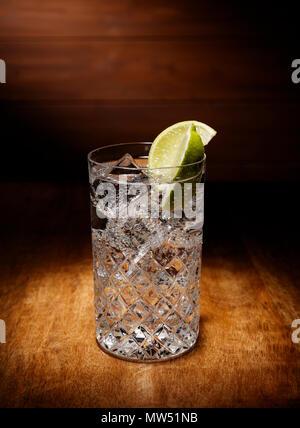 Riflettori puntati su un singolo bicchieri pieni di gin tonic cocktail, con un calce guarnire, girato su un antico tavolo di legno alto. Foto Stock