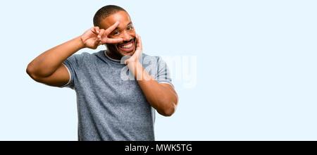 African American uomo con la barba guardando la telecamera attraverso le dita nel gesto di vittoria con una strizzatina d'occhio l'occhio e soffiando un bacio isolate su sfondo blu Foto Stock