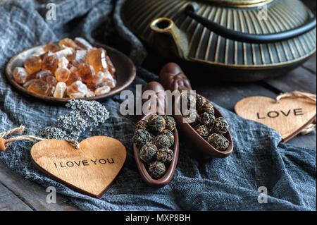 Una tazza di infuso di tè nero. Due spatole in ceramica con caramello di zucchero e foglie di laminati in un grande perla. Il tè cinese dal Yunnan. Bi Lo Chun Foto Stock