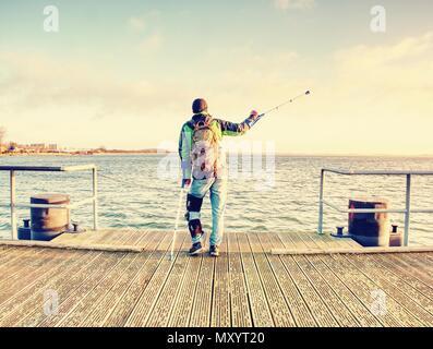 Escursionista con la medicina stampella e gamba fissata in un immobilizzatore a piedi su wharf Pier. L'uomo ha fissato gamba rotta in gesso. Felice l'uomo disabili sulla spiaggia a piedi. Len Foto Stock