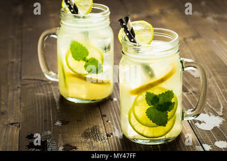 Il freddo limonata fresca cocktail mojito con ghiaccio, succo di limone e foglie di menta in Mason Jar sul rustico in legno scuro dello sfondo. Concetto di estate. Foto Stock