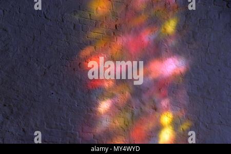 Extreme multicolore di luce riflessa in una chiesa, i riflessi di luce attraverso un vetro colorato su un bianco muro di mattoni in una chiesa Foto Stock