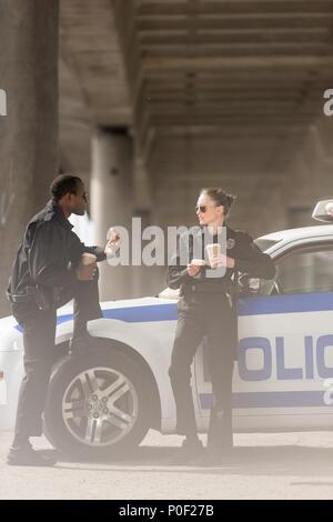 I funzionari di polizia con caffè e ciambelle in piedi accanto a AUTO sotto il ponte Foto Stock