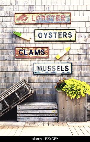 Vecchi segni e la pesca galleggianti su di un legno parete di ciottoli. Frutti di mare avvisi per le aragoste, cozze, ostriche e vongole con una trappola a base di aragosta e casse. Foto Stock
