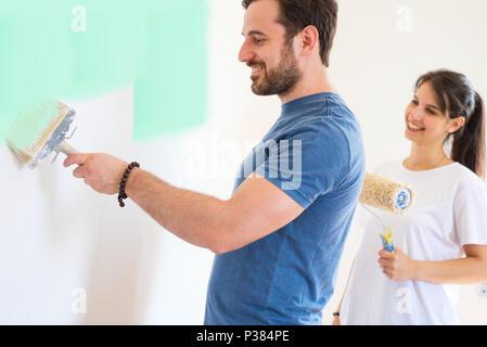 Coppia felice pittura pareti nella loro nuova casa pronta per vivere insieme Foto Stock