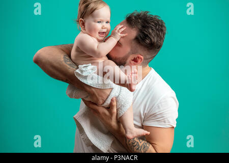 Giocoso padre portando la sua sorridente neonato sul collo su sfondo blu Foto Stock