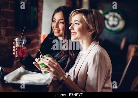 Due amiche avente cena con sandwich di verde in burger bar. Foto Stock