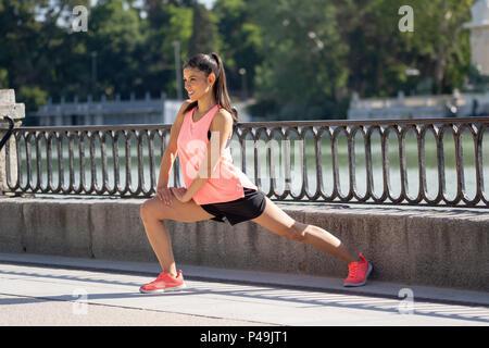 Giovane attraente femmina latina allenamento fitness prima sessione di formazione presso il parco con un lago sano giovane donna riscaldamento fino all'aperto in stretching egli Foto Stock