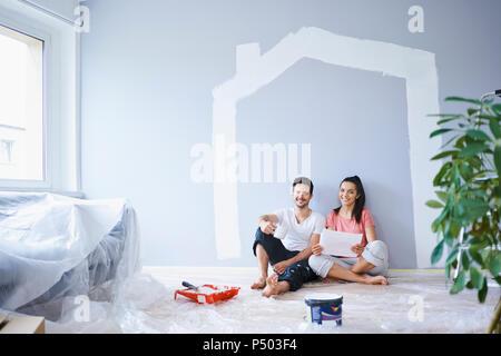 Coppia felice prendendo break dalla pittura pareti in un nuovo appartamento Foto Stock