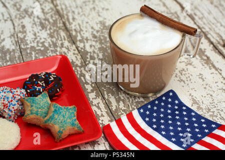 Bandiera americana igienico caffè o un cappuccino e i cookie su un rustico in legno bianco sullo sfondo. Seduto sulla parte superiore della tazza di vetro è un bastoncino di cannella si siede. Foto Stock