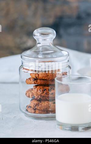 American biscotti al cioccolato con bicchiere di latte su una pietra bianca dello sfondo. Vista superiore e spazio di copia. Foto Stock