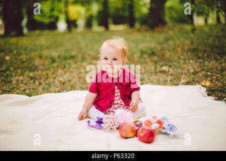 Little Baby girl etnia caucasica biondino di un anno dalla nascita si siede su un plaid sul prato verde nel parco e tiene in mano le mele rosse. Foto Stock