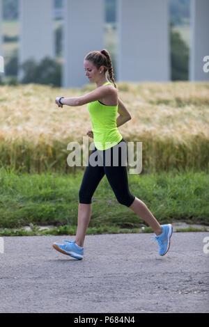 Giovane donna jogging, esecuzione, controllo i suoi segni vitali su un orologio fitness, fitness tracker, frequenza cardiaca, il numero di passi, distanza, tempo, calorie burn Foto Stock