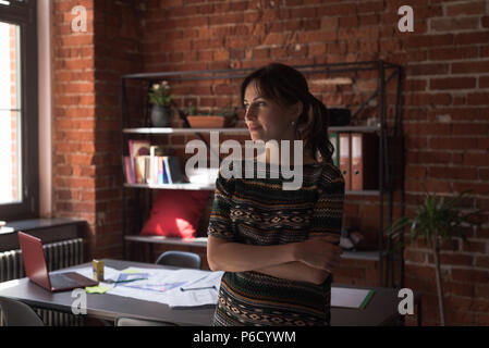Executive femmina in piedi con le braccia incrociate in office Foto Stock