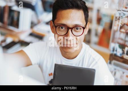 Giovani accattivante spectacled uomo sorridente e azienda prenota in mani. Foto Stock