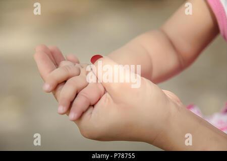 Madre tenendo il suo bambino canto close-up. Foto Stock