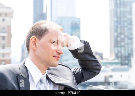 Bello e attraente lato giovane imprenditore profilo closeup volto ritratto in piedi in tuta, cravatta, guardando a New York City cityscape skyline di Manhatt Foto Stock
