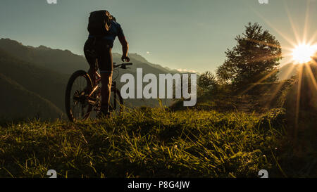 Un uomo biker sulla sua bike Mountain bike al Tramonto nelle Dolomiti le montagne delle Alpi Italia Foto Stock