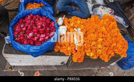 Pregando i fiori in vendita presso il tempio indù di Vecchia Delhi, India. Foto Stock