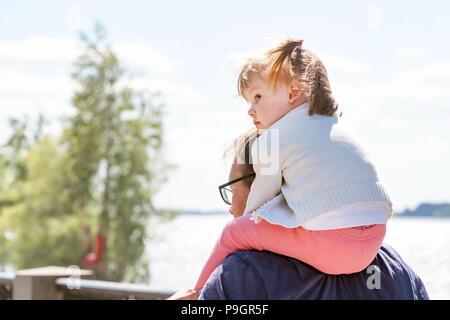 Piccola ragazza seduta al papà sul collo Foto Stock
