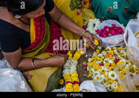 Donna indiana rendendo tradizionali di ghirlande di fiori in un mercato in stallo la Vecchia Delhi, Delhi, India Foto Stock