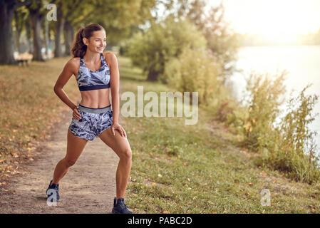 Montare muscolare di una donna che lavora fuori in un parco su un sentiero a fianco di un tranquillo lago o fiume facendo esercizi di stretching in una salute e concetto di fitness Foto Stock