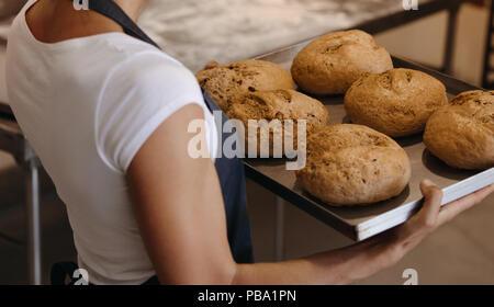 Close up baker femmina tenendo un pane appena sfornato su un vassoio da forno. La donna che porta un vassoio con pane cotto in un forno. Foto Stock