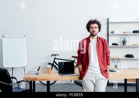 Bel giovane in occhiali appoggiata al tavolo e guardando la telecamera in ufficio Foto Stock