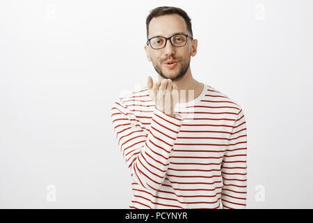 Invio di baci per te. Ritratto di carino bella gay uomo in bicchieri, azienda palm vicino a bocca di soffiaggio e mwah in telecamera con un leggero sorriso, mostra Foto Stock
