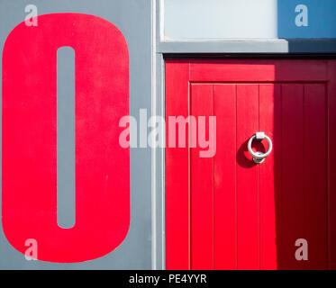 Colore close up di un rosso porta di legno con un round porta metallica respingente, accanto al grigio di una parete dipinta con un grande dipinto di rosso zero su di esso Foto Stock