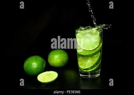 Estate rinfrescanti bevande e concetto. Bicchiere di bibita con ghiaccio e fresche e mature green slice limes su sfondo nero. Limonata fatta in casa. Il Mojito Foto Stock