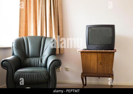 Televisione Vintage in legno antico armadio, vecchio design nel soggiorno con sedia antica Foto Stock