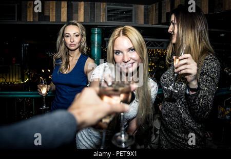 Parte delle ragazze in un ristorante che celebra con bevande e champagne Foto Stock