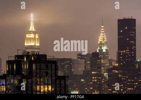 L'Empire State Building e il Chrysler Building illuminato di notte come visto dalla città di Long Island, Queens, a New York City. Foto Stock