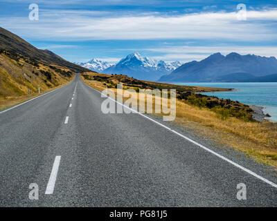 Nuova Zelanda, Isola del Sud, strada vuota con Aoraki Monte Cook e il Lago Pukaki fino in background Foto Stock