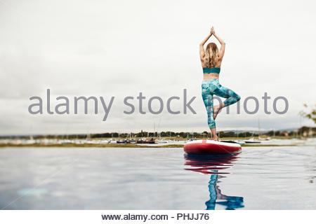 Giovane donna fare yoga su un paddleboard Foto Stock