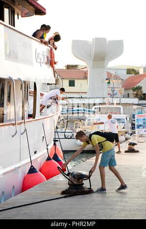 Vodice Croazia - Agosto 11, 2018: una nave da crociera di Carpe Diem arrivando a Vodice e docking. Un uomo e un ragazzo adolescente su un molo il fissaggio della corda di nave Foto Stock