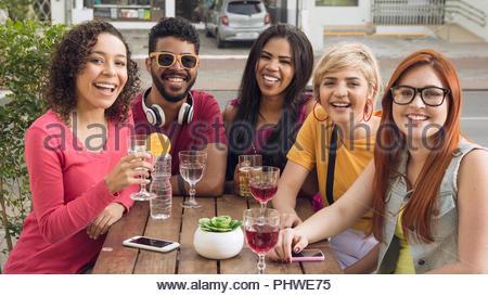 Allegro giovani amici avente un grande tempo presso il cafe bar all'aperto. Gruppo di persone socializzazione in un party al ristorante esterno. Estate, caldo, amicizia Foto Stock