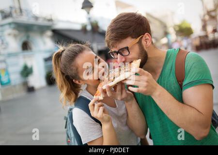 Allievi felici di mangiare la pizza su strada Foto Stock