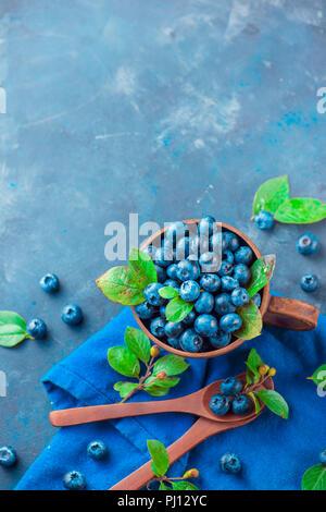 Estate bacche laici piana. I mirtilli in una coppa in ceramica con cucchiai di legno dal di sopra. I colori neutri, blu e grigio tavolozza, spazio copia Foto Stock