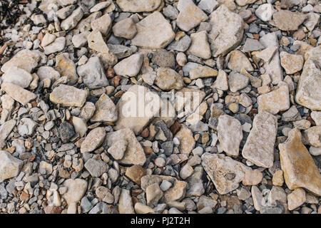 Guardando verso il basso in corrispondenza della superficie di una spiaggia rocciosa con molte rocce, pietre e ciottoli di diverse forme e dimensioni in mute marrone e arancione Foto Stock