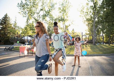 La madre e le figlie jump roping al quartiere estivo block party in strada Foto Stock
