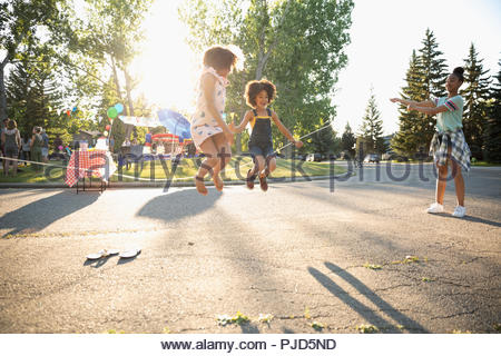 Carino sorelle jump roping al quartiere estivo block party in sunny street Foto Stock
