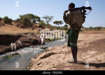 Un Turkana armati giovane veglia sull' allevamento di capre di bere da un fiume vicino a Isiolo, nel nord del Kenya, 28 marzo 2012. Foto Stock