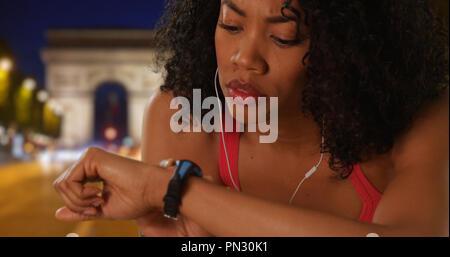 Close up nero donna controllo tracker fitness sugli Champs Elysees a notte Foto Stock