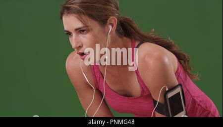 Giovane donna millenario controllo idoneità tracker sul polso sul schermo verde Foto Stock