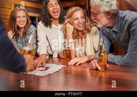 Amici a giocare gioco di carte in tavola di cabina Foto Stock