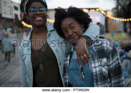 Ritratto fiducioso e sorridente sorelle avvolgente al film nel parco Foto Stock