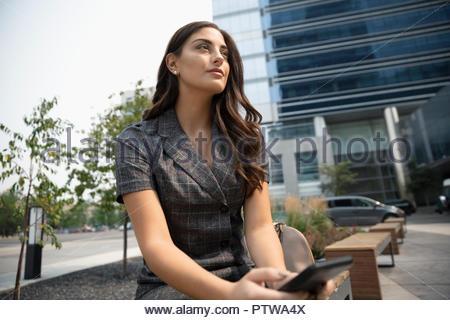 Riflessivo imprenditrice utilizzando smart phone in ambiente urbano plaza Foto Stock