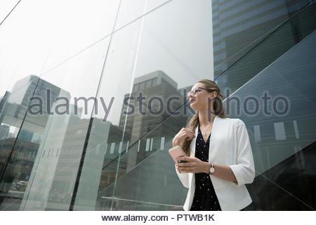 Riflessivo imprenditrice con smart phone extra urbana edificio per uffici Foto Stock